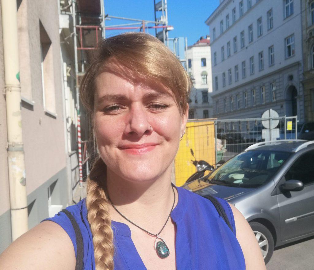 Das Bild zeigt ein Selfie von Lorena Hoormann auf der Straße, im Hintergrund ist ein Auto und eine Baustelle zu sehen. Der Himmel ist blau, die Sonne scheint.