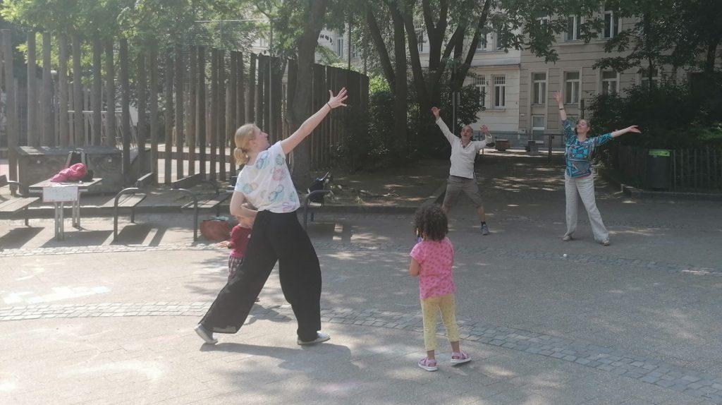 Das Bild steigt tanzende Menschen mit nach oben seitlich weit ausgestreckten Armen in eienm Park. auch Kinder sind dabei.