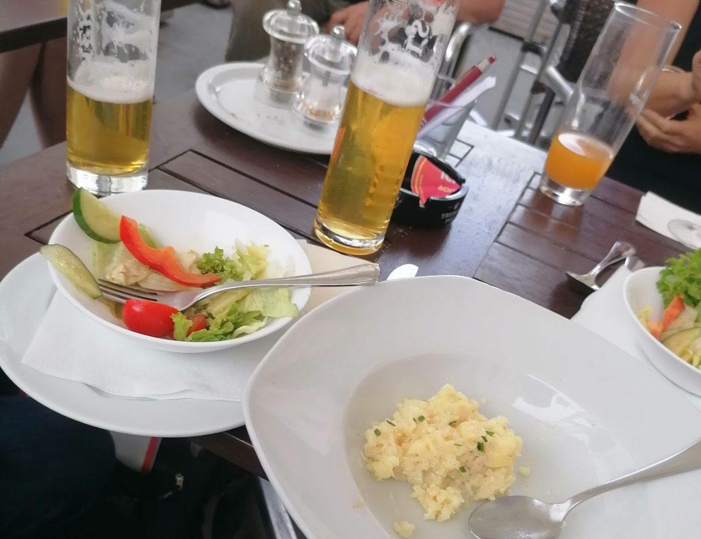 Das Foto zeigt einen Tisch, darauf 2 Biergläser, ein fast leerer Spinat-Risotto-Teller, ein Salat.