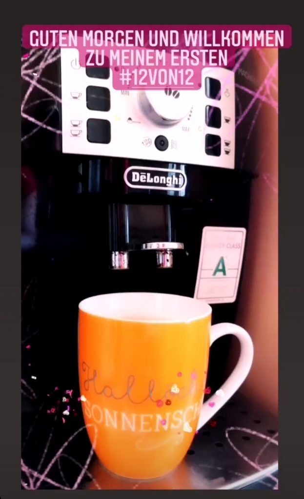 Das Bild zeigt eine orangenen Becher mit der Aufschrift Hallo Sonnenschein, unter der Kaffeemaschine von de Longhi.