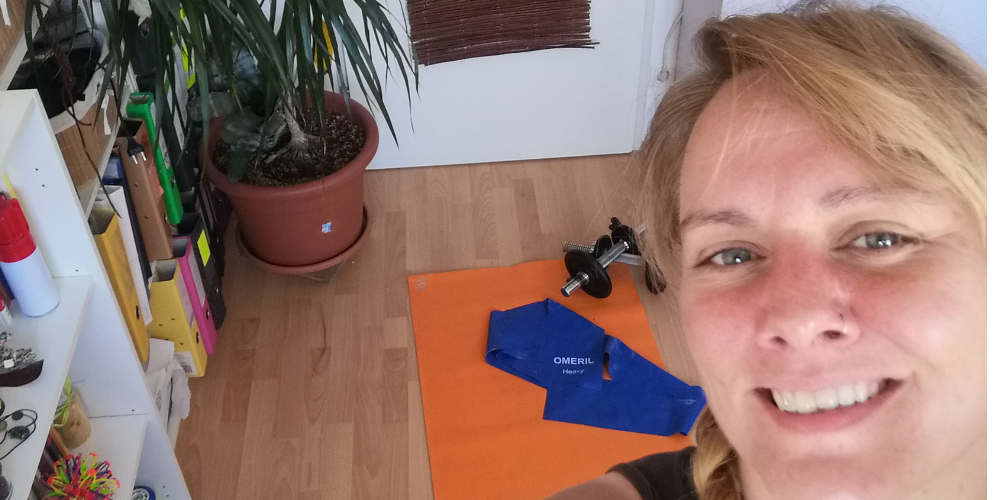 Das Bild zeigt ein Selfie von Lorena von schräg oben, am Boden liegt eine orangene Yogamatte, dazu ein Terraband und Gewichte.